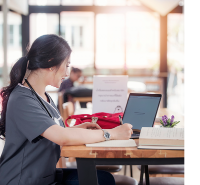UConn Healthcare Innovation Online Graduate Certificate: Nurse working at laptop in hospital commissary
